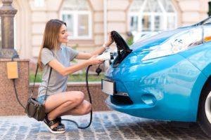 Femme rechargeant sa magnifique voiture électrique
